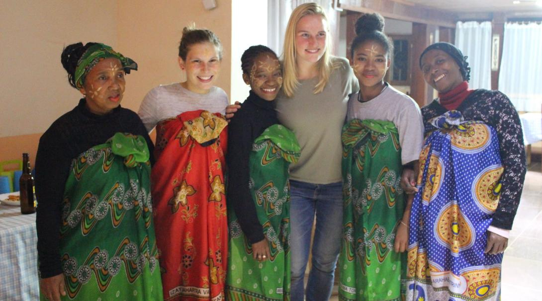 Projects Abroad volunteers posing with a family in Madagascar wearing traditional Malagasy clothing